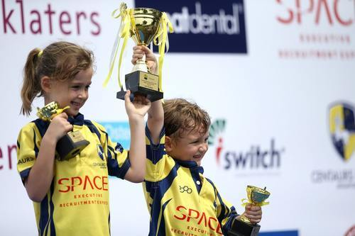 2 young rugby players with trophees