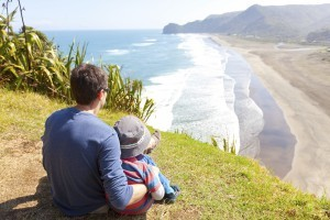 Man and child viewing beach off New Zealand bluff