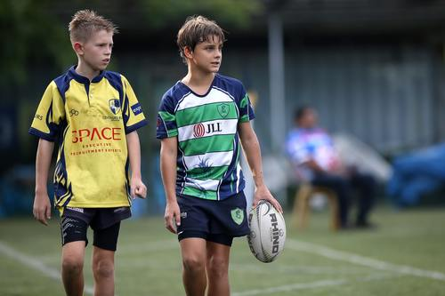 2 boys walking with rugby ball and kit