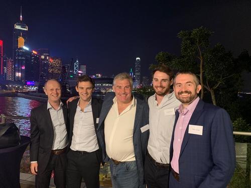 men smiling at camera with hong kong skyline backdrop