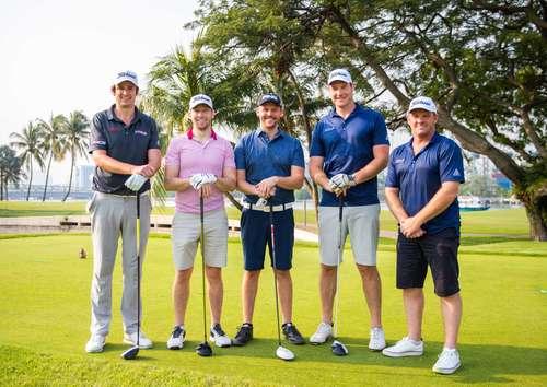 5 golfers smiling at camera