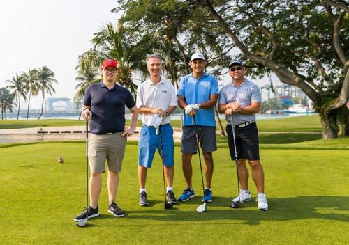 4 golfers smiling at camera