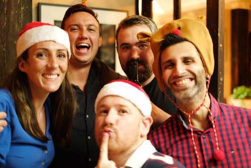group of people smiling at camera with christmas hats