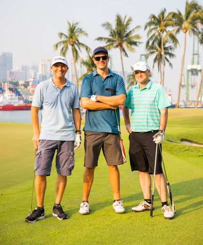 3 golfers smiling at camera
