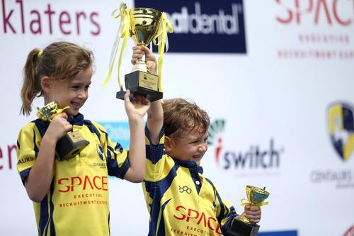young boy and girl holding trophee
